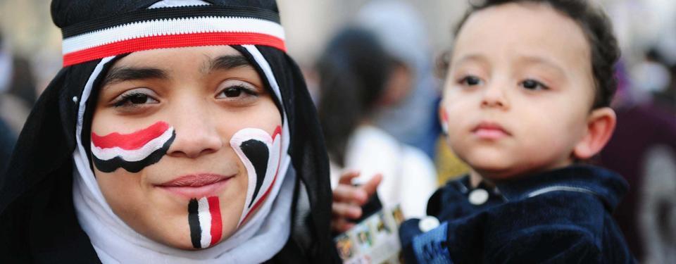 Bilden visar en kvinna som håler i sitt lilla barn. Kvinnan är målad i egyptens flaggas färger.