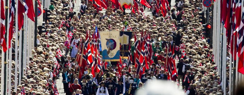 Bilden visar en flaggprydd gata fylld av mängder av människor, många flaggbärande.