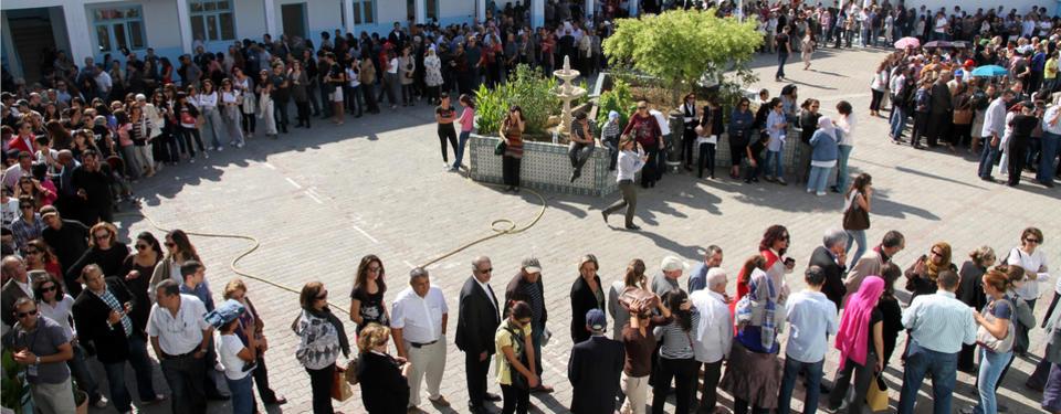 Bilden visar en stor mängd människor på led i flera rader kring en öppen plats.