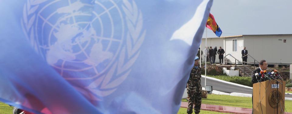 Bilden visar en man ståendes vid talarpulpet fylld med mikrofoner, en soldat ståendes bakom och större delen av bilden täckt av FN flaggan.