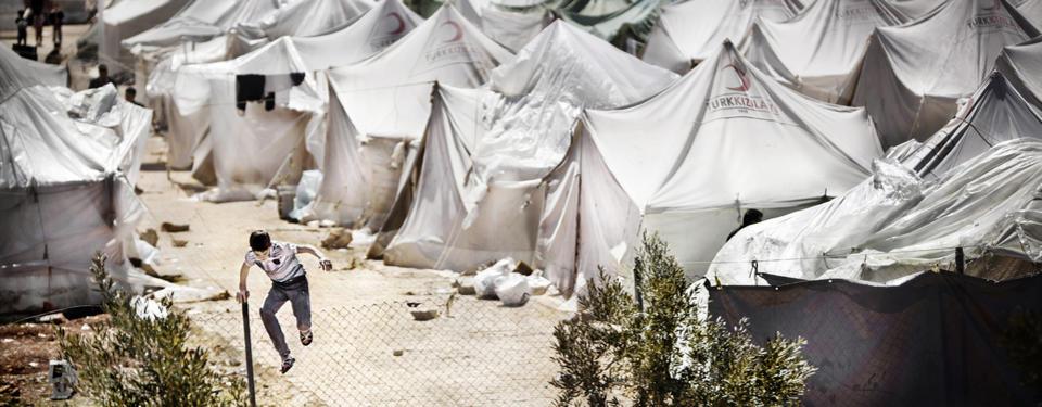 Bilden visar en yngre pojke och flera vita tält i bakgrunden.
