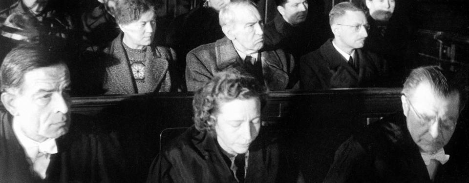 Bilden visar 5-6 män och 2-3 kvinnor som sitter i tre bänkrader och ser allvarsamma ut.