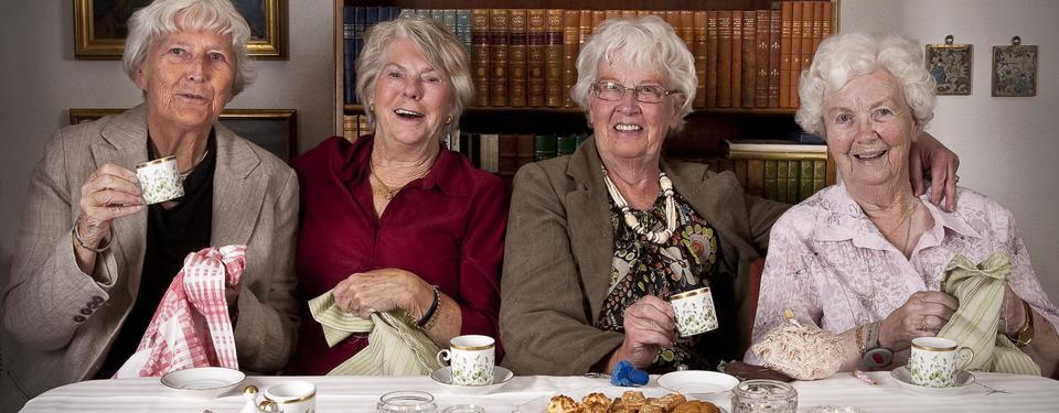 Bilden visar fyra äldre, vithåriga kvinnor sittandes och fikar.