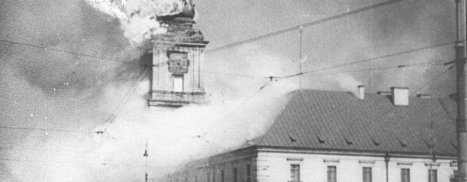 Bilden visar ett hustak med rök från samt ett klocktorn i eldslågor och rök.