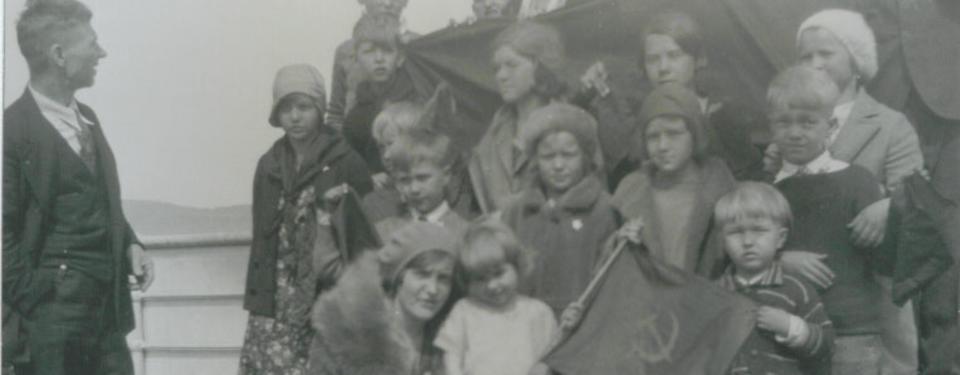 Bilden visar en gruppbild på ett femtontal personer och en man ståendes betraktandes dem.