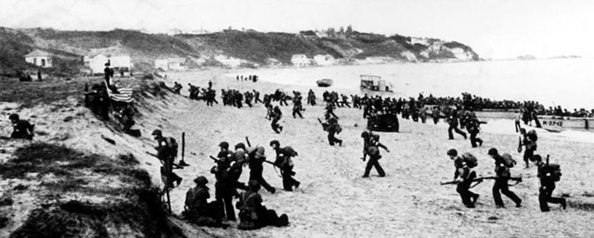 Bilden visar större mängd soldater på strandremsa.