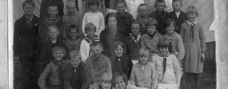 Bilden visar en gruppbild på ett tjugofemtal barn med yngre kvinna i mitten.