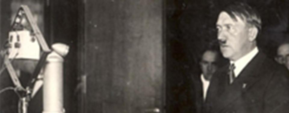 Hitler står famför en radiomikrofon.