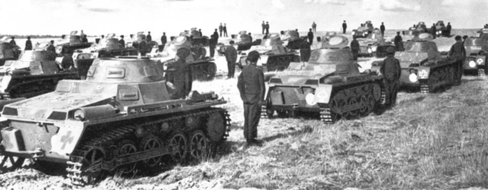 Bilden visar ett tjugotal pansarvagnar på fält med en soldat ståendes mellan varje fordon.