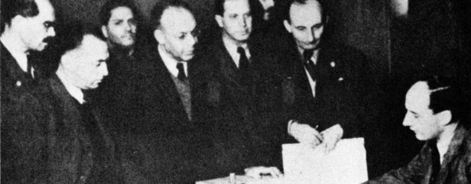 Bilden visar Raoul Wallenberg sittandes vid bor och sju män ståendes framför.