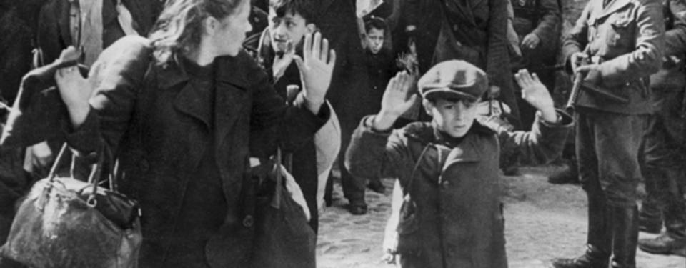 Bilden visar en pojke och en kvinna i närbild med händerna i luften och en soldat pekandes sitt vapen mot dem.