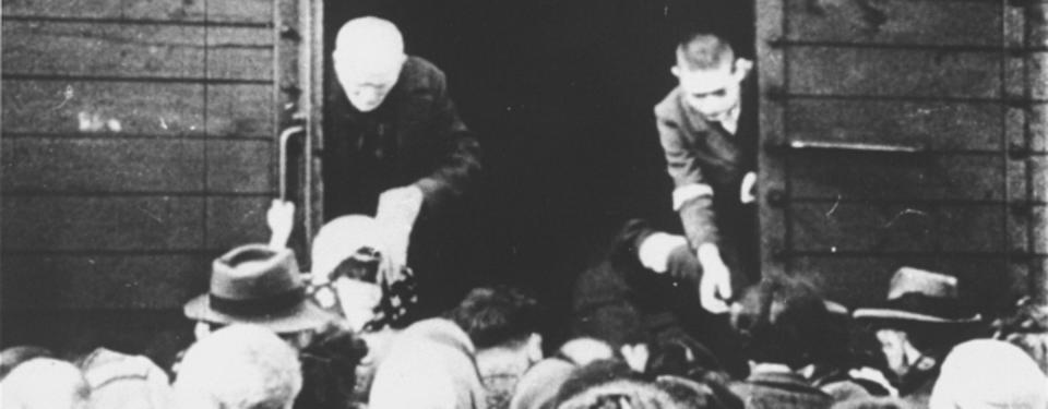 Bilden visar en äldre och en yngre man ståendes i öppningen av tågvagn med många människor utanför.