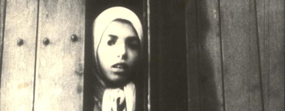 Bilden visar porträtt av ett barn klädd i huvudduk.