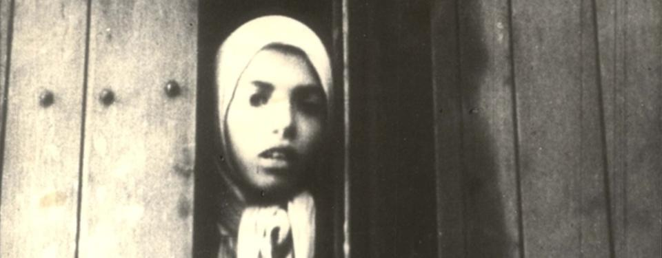 En svartvit bild på en flicka med sjalett som tittar ut från en tågvagn.