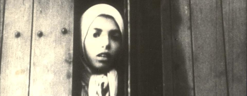Bilden visar ett svartvitt foto på en flicka som tittar ut genom en tågvagn.
