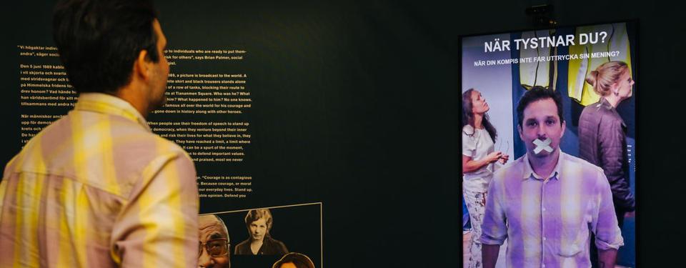 Bilden visar människor i en utställning med texten: När tystnar du?