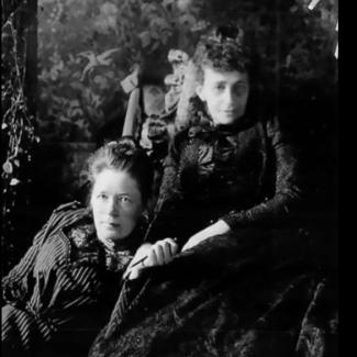 Bilden föreställer två äldre kvinnor som sitter nära varandra.