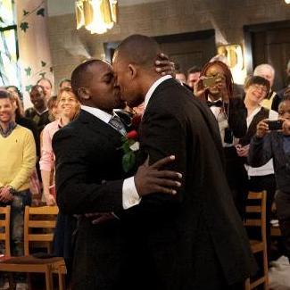 Bilden visar två män som kysser varandra.