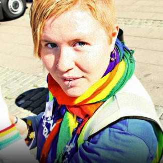 Bilden visar en person med en regnbågsfärgad halsduk.