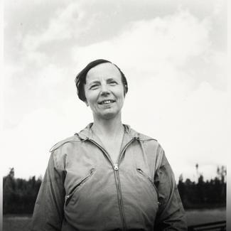Fotografiet är svartvitt och visar en leende kvinna utomhus.